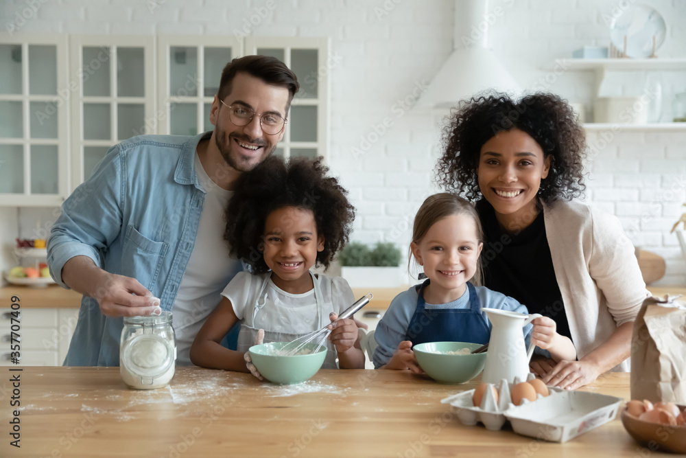 Fototapeta Multiethnic family with kids engaged in holiday cake preparation using fresh products mixing eggs milk flour ingredient looking at camera. Teach children, happy parenthood, common hobby, unity concept