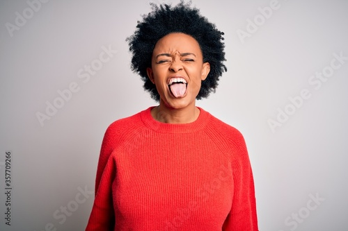 Obraz na plátne Young beautiful African American afro woman with curly hair wearing red casual sweater sticking tongue out happy with funny expression