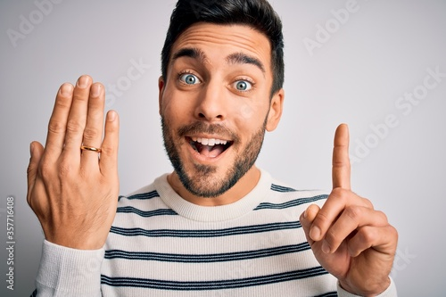 Photo Handsome man with beard showing alliance ring marriage on finger over white back