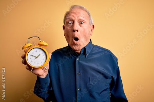 Senior grey haired man holding vintage alarm clock over yellow background scared Wallpaper Mural