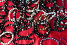 High Angle Shot Of Colorful Bead Bracelets On A Red Tablecloth On The Table Under The Lights