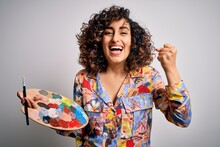 Young Beautiful Curly Arab Artist Woman Painting Using Brush And Palette With Colors Screaming Proud And Celebrating Victory And Success Very Excited, Cheering Emotion