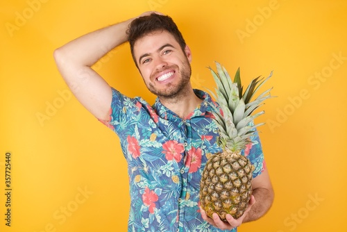 Portrait of handsome caucasian male looks with excitement at camera, keeps hands raised over head notices something unexpected, isolated over gray wall Tapéta, Fotótapéta