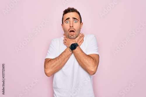 Handsome man with blue eyes wearing casual white t-shirt standing over pink background shouting and suffocate because painful strangle Canvas Print