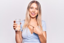 Young Beautiful Blonde Girl Drinking Glass Of Water Smiling Happy Pointing With Hand And Finger