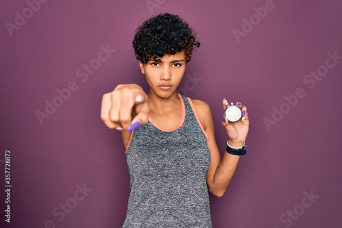 Young beautiful african american sporty woman holding stopwatch over purple back Canvas Print