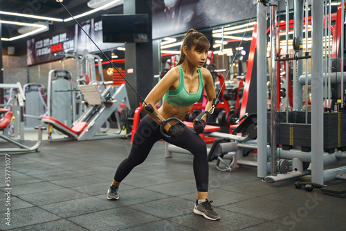 Asian young woman doing elastic rope exercises at cross fitness gym Billede på lærred