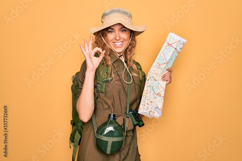 Foto Young blonde explorer woman with blue eyes hiking wearing backpack holding city