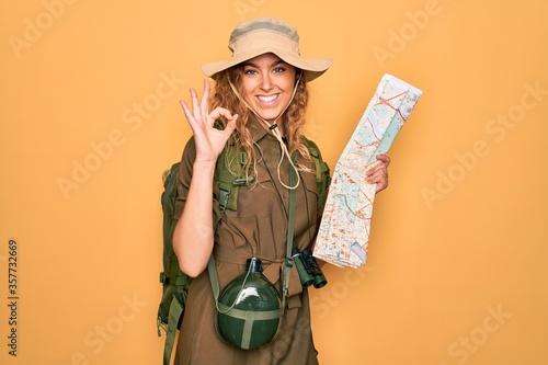 Slika na platnu Young blonde explorer woman with blue eyes hiking wearing backpack holding city