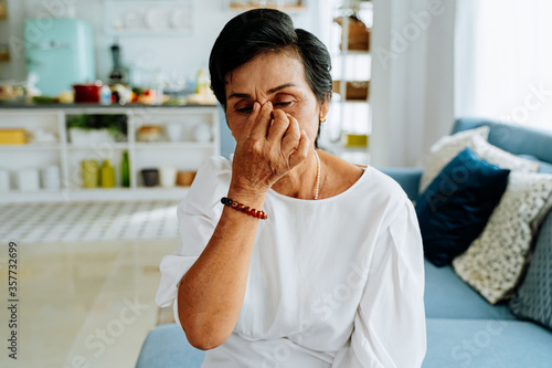 Fototapeta Mature Asian lady with closed eyes rubbing nose while sitting on sofa and suffering from headache in cozy living room at home obraz