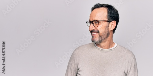 Fotografie, Obraz Middle age handsome man wearing casual sweater and glasses over isolated white background looking to side, relax profile pose with natural face and confident smile