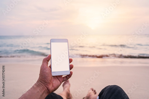 Foto Young man traveler using  smartphone at tropical sand beach, Summer vacation con