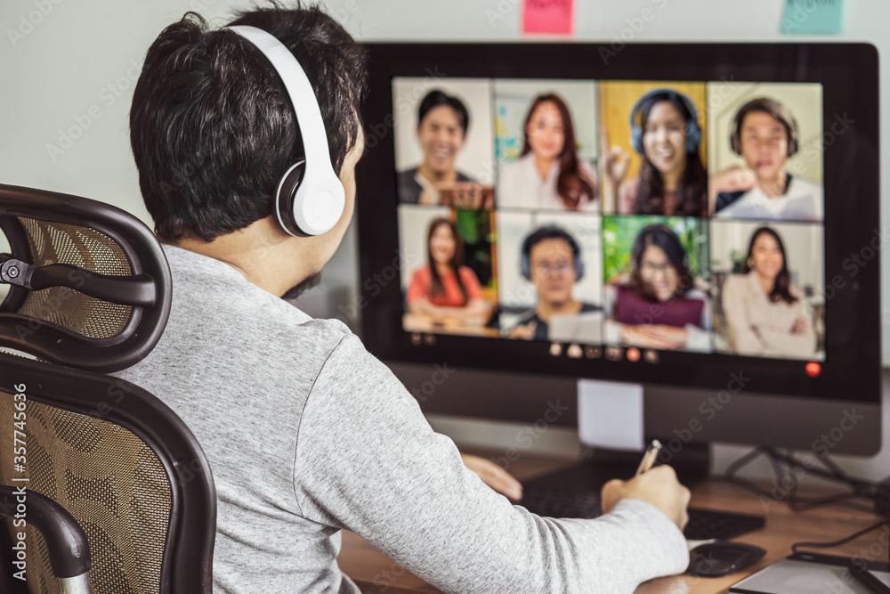 Fototapeta Rear view of Asian man working and online meeting via video conference with colleague and team building when Covid-19 pandemic, Coronavirus outbreak, education and Social distancing,new normal concept
