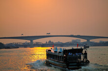 A Ferry On A River At Sunset