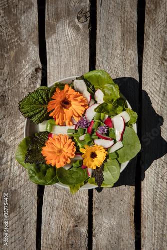 Schale mit Salat auf braunem Holzuntergrund #357754480