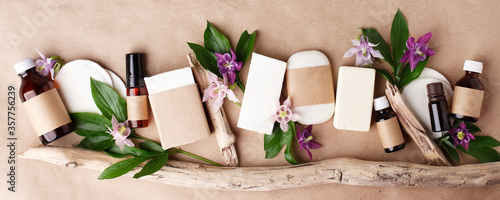Fotografía Herbal natural facial cosmetic products set with herbs and flowers on paper craft background, top view
