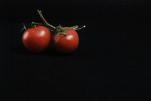 Closeup Shot Of Two Cherry Tomatoes Isolated On A Black Background