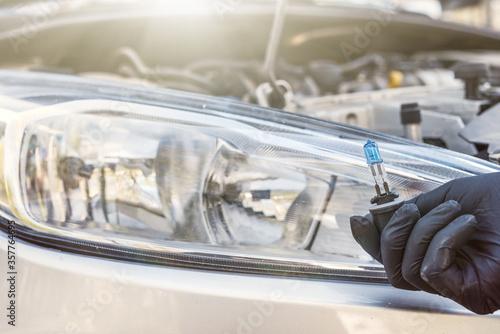 Obraz Mechanic installing changing modern halogen headlight bulb - fototapety do salonu