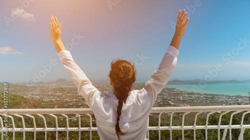 Photo woman in white blouse raises hands admiring picturesque landscape with blue ocea