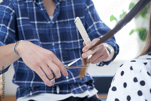 Obraz 美容室で髪の毛を切る爽やかな美容師 - fototapety do salonu