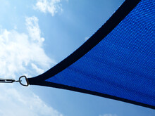 Weaved Breathing Blue Fabric Sun Shade Material. Patio Awning. Spanning Over Terrace. Blue Sky And White Clouds. Abstract Low Angle View. Metal Connector And Chain. Summer And Outdoors Concept.