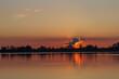 Standing paddler on the lake at sunset