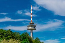 A Radio Tower With A Blue Sky And A Few White Clouds.