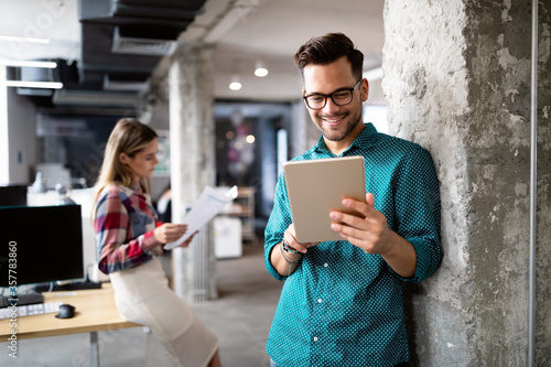 Young man using technology, digital tablet in corporate business office Fototapeta