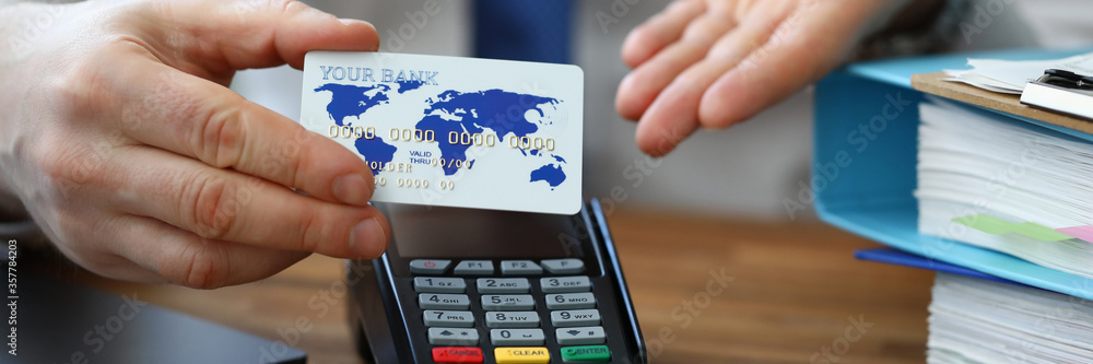 Fototapeta Man holds credit card in his hand, near terminal. Bank employee explains how to pay by credit card through wireless terminal. Advantages acquiring for business. Terminal service fee
