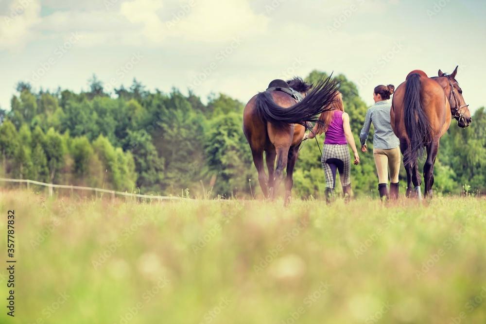 Fototapeta Young girls riding horses bareback in field