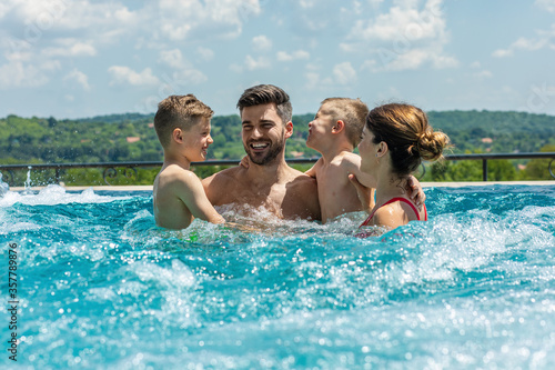Fotografia Smiling family of four having fun and relaxing in outdoor swimming pool at hotel resort