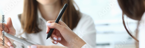 Focus on tender hands of female businesspeople holding important corporate documents and pointing at charts and graphs with writing metallic pen Fototapet