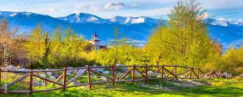 Obraz Bansko, Bulgaria spring landscape with the wooden fence, trees, tower of chalet and snowy Rila mountains peaks - fototapety do salonu