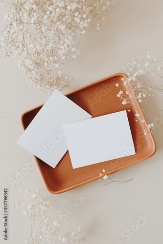 Fototapeta Blank paper sheet cards with mockup copy space and gypsophila flowers bouquet on neutral beige background