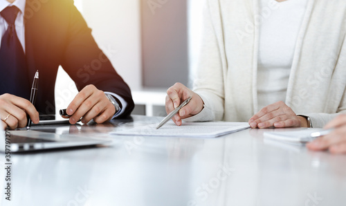 Fototapeta Business people discussing contract while working together in sunny modern office. Unknown businessman and woman with colleagues or lawyers at meeting obraz