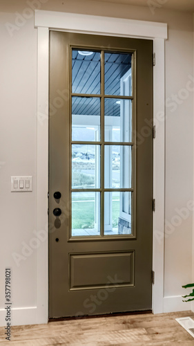 Obraz na plátne Vertical Hinged front door with glass pane viewed from interior of home with woo