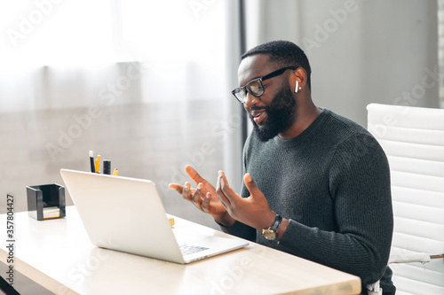 Side view of African-American office employee talking via video connection while sitting at the desk Fototapete