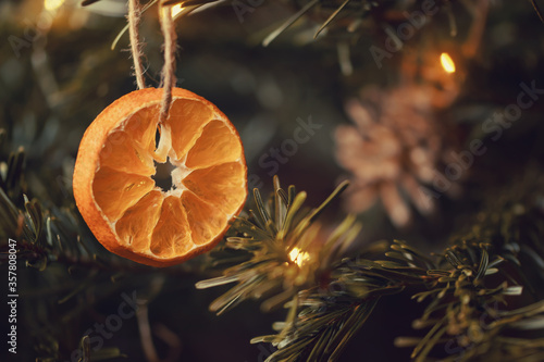 Fototapeta Zero waste christmas concept. Christmas tree decorated with ornaments made of natural materials - slices of dried orange and cones obraz