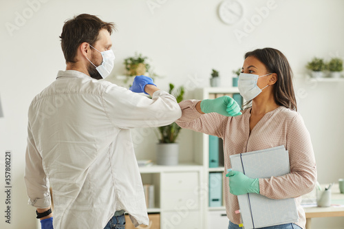 Fototapeta Waist up portrait of two colleagues wearing face masks bumping elbows while greeting each other at work in office obraz