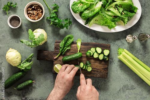 Fotografie, Obraz Healthy vegan food vegetables nuts seeds and cereals top view Male hand preparin