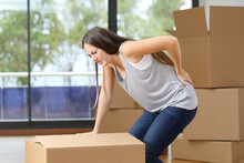 Woman Moving Boxes Suffering Backache At Home
