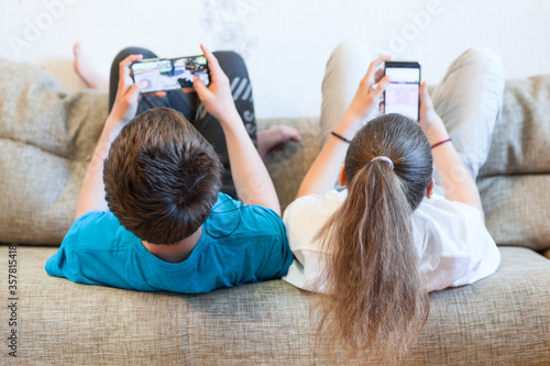 Sister and brother using their smartphones while lying back on couch at home Canvas Print