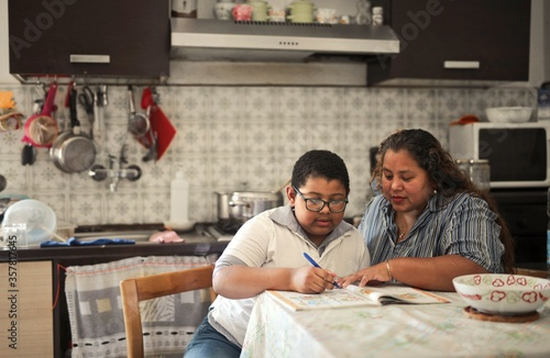 mother helps her son with schoolwork