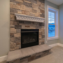 Square Modern Fireplace And Decorative Shelf Against Stone Brick Accent Wall Of Home