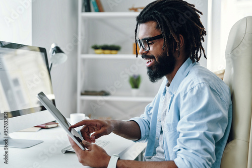 Happy young African man using digital tablet and smiling while working in the of Canvas-taulu