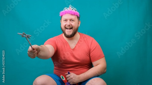 handsome bearded freaky man in a pink T-shirt with a diadem on his head is riding astride a unicorn with a magic wand in his hand Wallpaper Mural