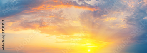 Fototapeta Cloudy dramatic sky with orange bright sun at sunset obraz