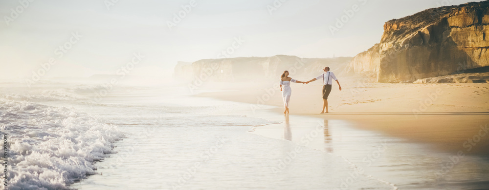 Fototapeta Man and woman have fun on the beach. Couple in love running at the beach.