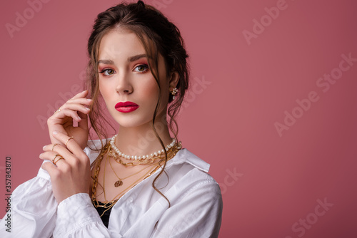 Foto Fashion, beauty portrait of elegant woman wearing trendy jewelry: river pearl earrings, necklace, chains, many golden rings