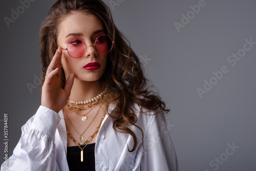 Fashionable model, woman wearing pink color sunglasses, trendy pearl necklace, many golden chains, classic white shirt Wallpaper Mural